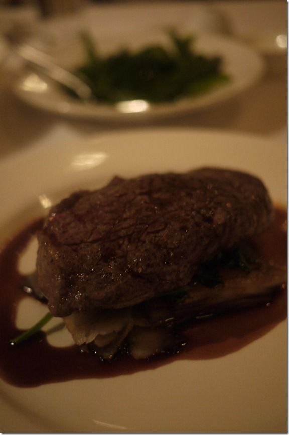 Sirloin steak in red wine reduction with spinach leaves and potato