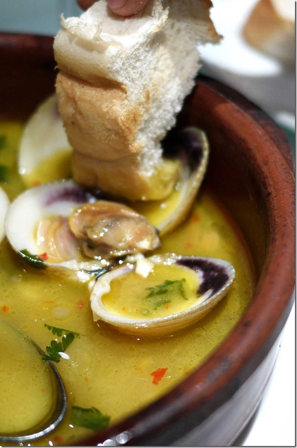 Dipping bread into the Portugalia clams broth