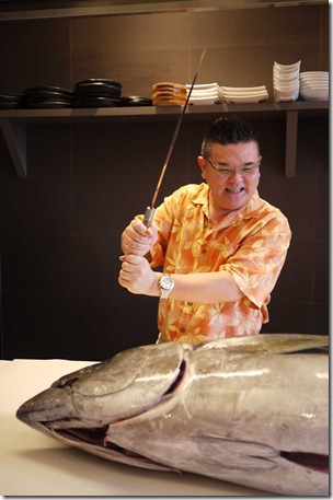 Terry Nishiura jokingly demonstrates how he prepares sushi