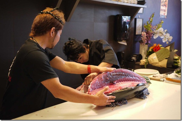 Sushi chefs meticulously slicing up the giant bluefin tuna