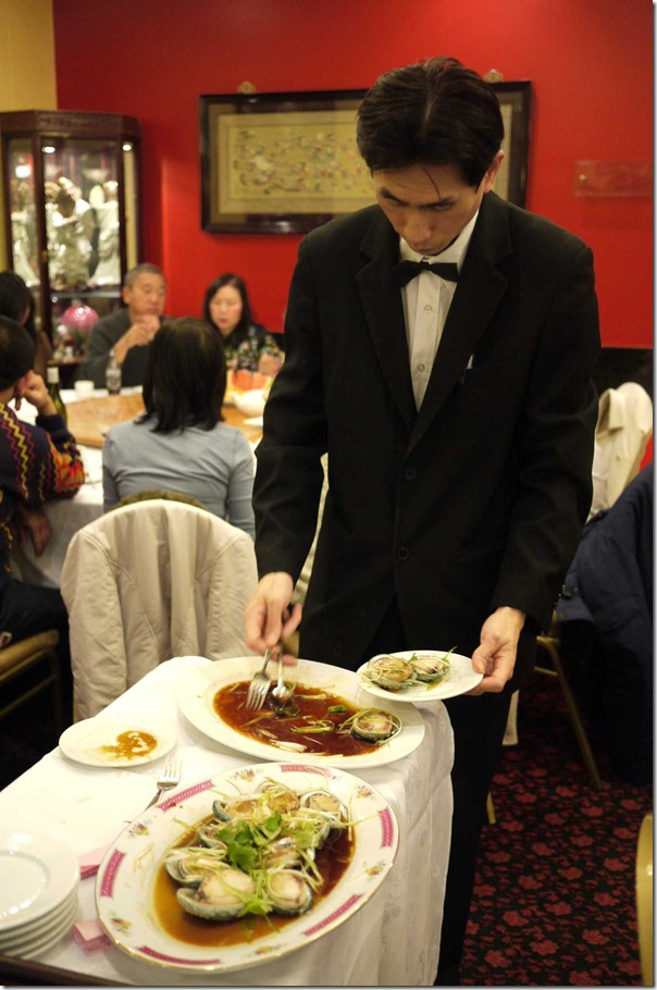 Waiter serving steamed abalone with ginger and shallots