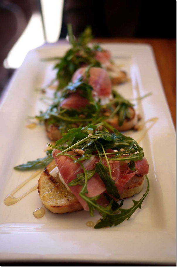 Breakfast bruschetta - goat cheese, prosciutto, pine nuts and rocket on toast