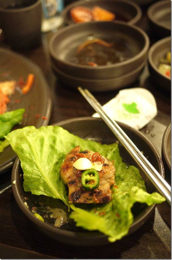 Korean BBQ chicken topped with, bean paste, raw garlic and green chilli in lettuce wrap