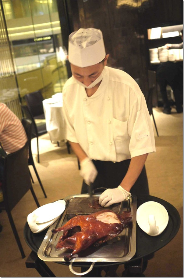 Peking duck chef carving up the bird