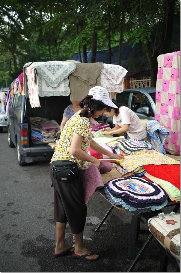 Street vendor selling floor mats off the back of a van