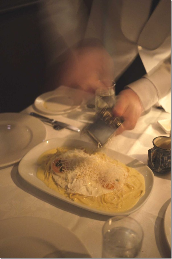 Freshly grated parmesan cheese is added to the pasta