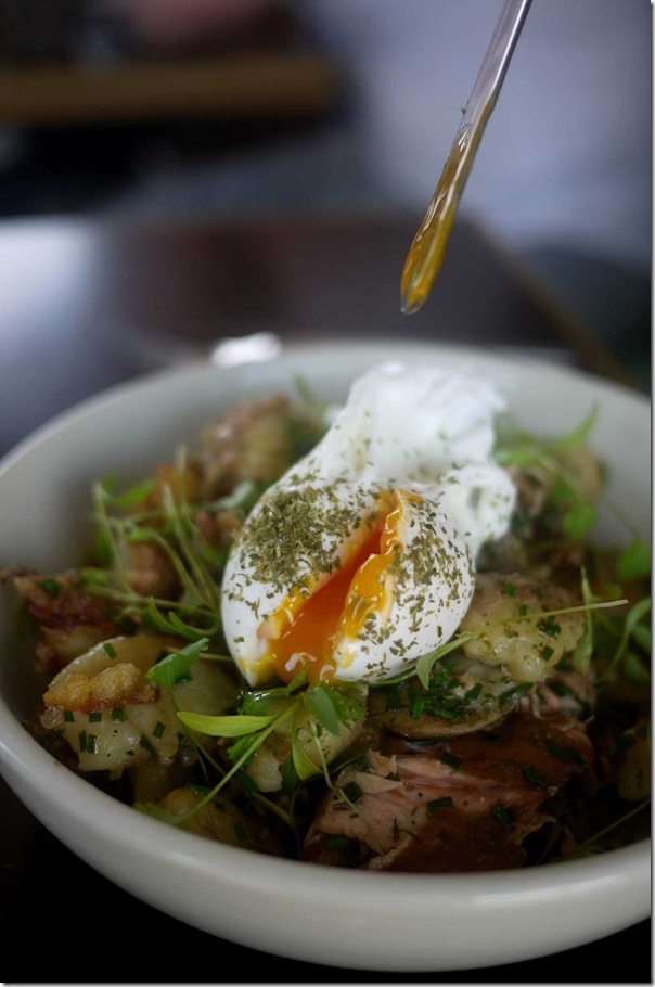 Poached egg on top of house-smoked salmon hash
