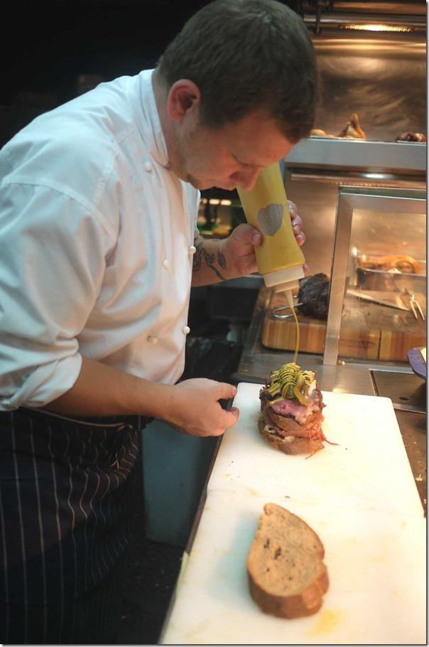 Brett Luckens preparing a Reuben sandwich