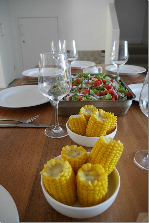 Corn on the cob and salad of cherry tomatoes, butter lettuce, onions and cucumber