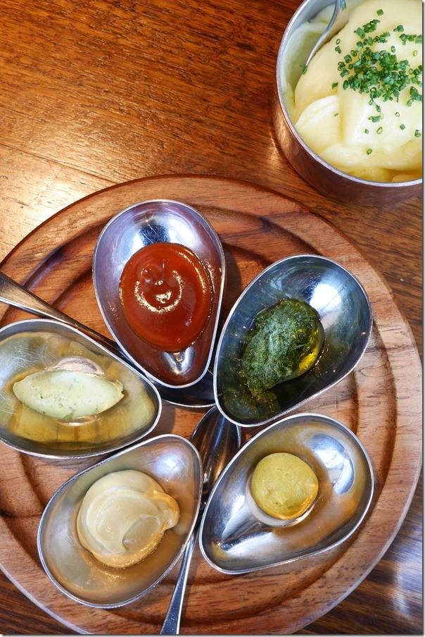 Clockwise from top: House-made steak sauce, salsa verde, French Dijon, Hot English, Cafe de Paris butter