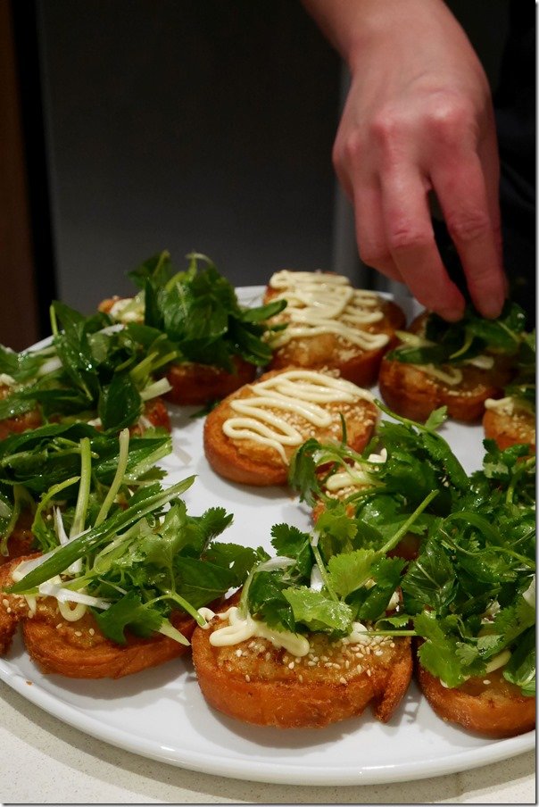 Garnishing prawn toast with spearmint, coriander and shallots