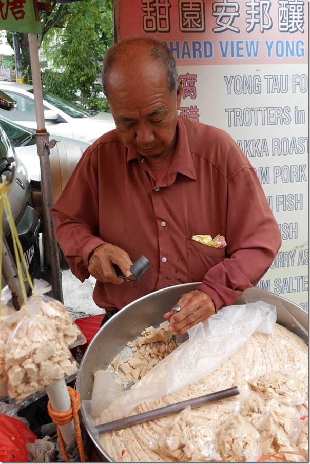"Street hawker chipping out ""ting ting thong"" or rock candy with a chisel"