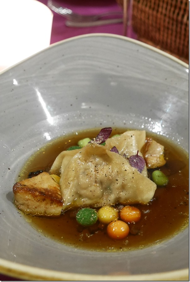 Rabbit ravioli, foie gras and crunchy vegetable pearls in truffle consommé