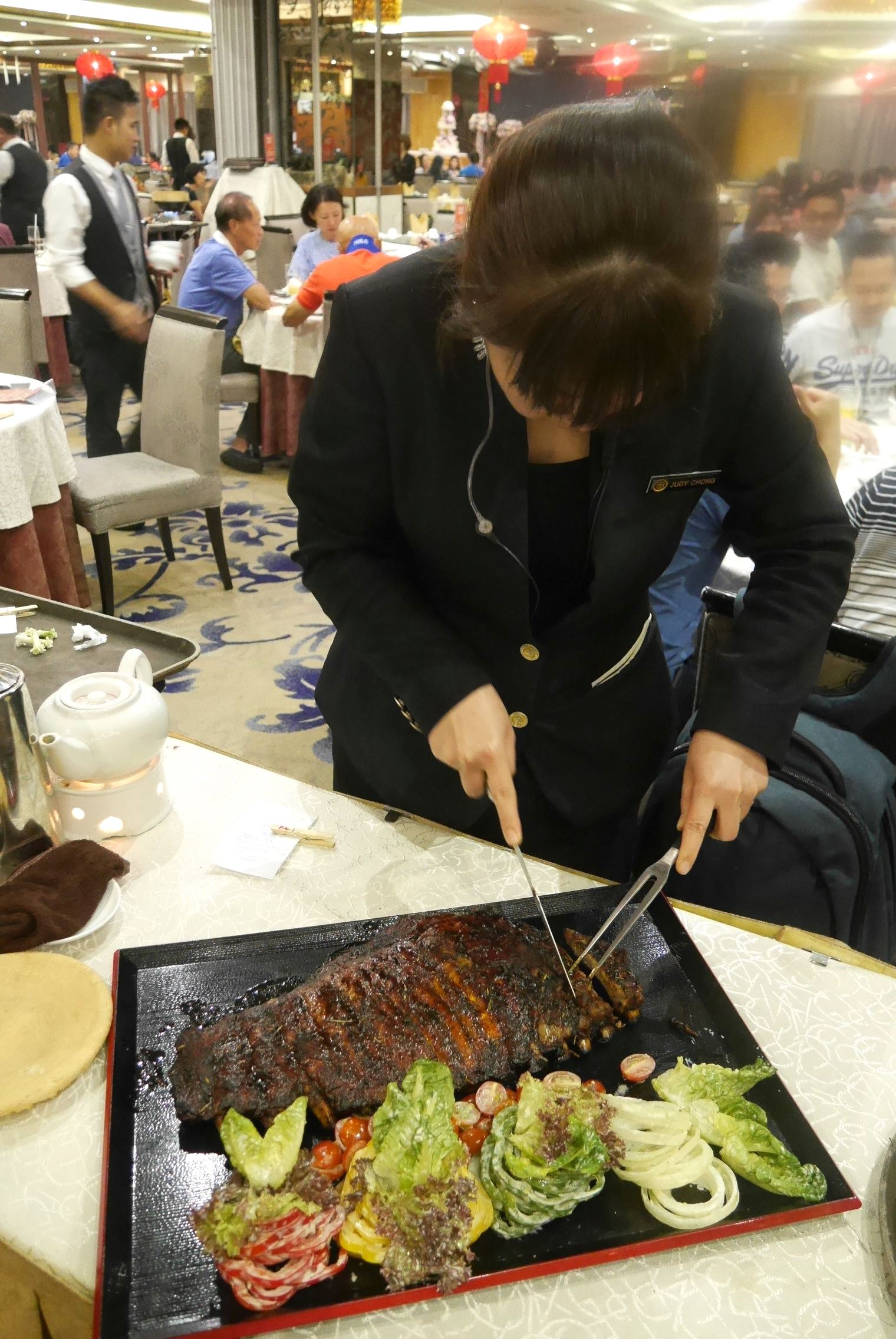 Head waitress cutting up Iberico grilled spare ribs